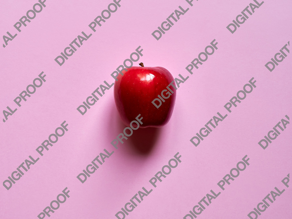 Red apple viewed from above over a pink background isolated in studio