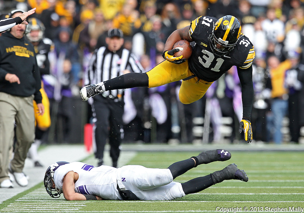 October 26 2013: Iowa Hawkeyes linebacker Anthony Hitchens (31) goes flying over Northwestern Wildcats quarterback Kain Colter (2) during the second quarter of the NCAA football game between the Northwestern Wildcats and the Iowa Hawkeyes at Kinnick Stadium in Iowa City, Iowa on October 26, 2013. Hitchens was running with the ball after what he thought was an interception. The pass was ruled incomplete.  Iowa defeated Northwestern 17-10 in overtime.