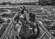 Fleuve Oyapock, 2015.<br /> <br /> Pirogue guyanaise « légale », franchissement d'un saut. Ici, pas de route, le transport fluvial représente la seule liaison régulière possible entre les communes enclavées le long de l'Oyapock. Ce fleuve est pourtant juridiquement considéré comme non navigable. <br /> <br /> La navigation sur l'Oyapock nécessite le franchissement de nombreux « sauts », des barrages naturels causes d'accidents à répétition. Les piroguiers doivent déterminer leur trajectoire sur un fleuve où aucun chenal n'est balisé et où de nombreuses roches affleurent et rendent la navigation difficile ou impossible. En saison sèche, les transports de fret doivent régulièrement déposer leur cargaison sur la berge, porter la pirogue par voie terrestre jusqu'à un point situé après le saut où la cargaison transportée à pied rejoindra la pirogue.<br /> En saison des pluies, il faut compter cinq heures pour rejoindre Camopi depuis Saint-Georges de l'Oyapock à deux cents kilomètres en aval si le voyage s'effectue sans encombre, en saison sèche, le même trajet peut durer deux ou trois jours.<br /> <br /> Dans ce contexte, dans les pirogues une certaine solidarité prévaut sur des considérations d'appartenance nationale, français guyanais, brésiliens clandestins ou pas et amérindiens partagent les mêmes contraintes.