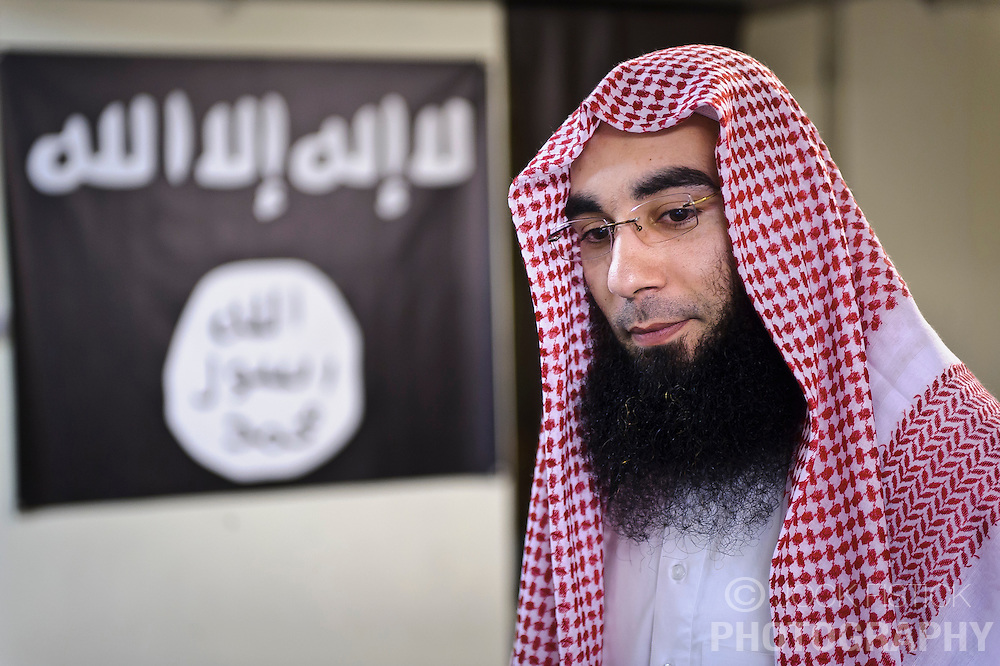 """Fouad Belkacem, a.k.a. Abu Imran, an Islamic extremist who is spearheading the movement """"Sharia4Belgium"""", poses in front of a flag commonly associated with al-Qaeda, at his headquarters in Antwerp, Belgium, on Tuesday, April 3, 2012. (Photo © Jock Fistick)"""