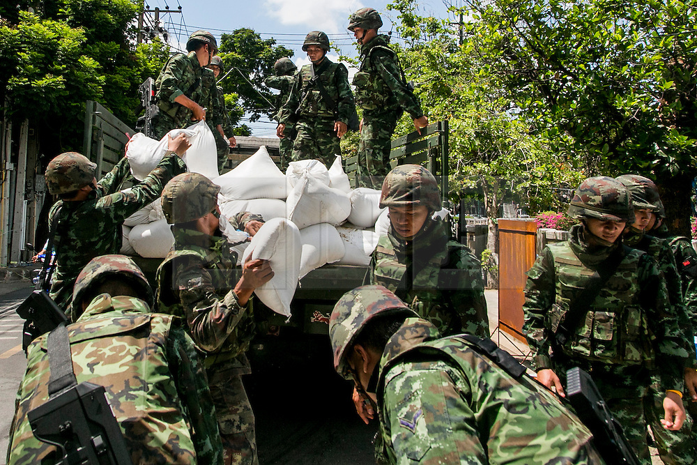 © Licensed to London News Pictures. 23/05/2014. Royal Thai army soldiers remove sandbag barricades built by PDRC protestors at their protest camp in Bangkok Thailand. Thailand's army said on May 23 that 155 prominent figures, including Yingluck and ousted government leaders, were banned from leaving the country without permission following a military coup.  Photo credit : Asanka Brendon Ratnayake/LNP