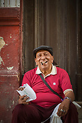 Mature man sitting outside building and selling cigars, Havana, Cuba
