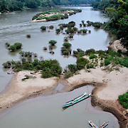 In the foreground, wooden canoes are moored on riverbank of Nam Ou (River Ou) in Nong Khiaw in northern Laos. The sandy bottom of the river means that the current creates small, sandy islands and protected inlets on the river.