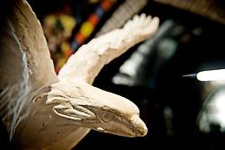 """Un dettaglio dell'acquila ai piedi della statua della Libertà in miniatura nella casa museo all'interno di """"Vincent City"""", residenza del pittore salentino """"Vincent Brunetti""""nei pressi di Guagnano in provincia di Lecce. 29/03/2009 (PH Gabriele Spedicato) ..VINCENT BRUNETTI.Affettuosamente identificato con l'appellativo """"LA LIBELLULA DEL SUD"""", Vincent Brunetti è oggi considerato uno dei personaggi più emblematici della vita artistica meridionale..Nato a Guagnano di Lecce il 3 dicembre 1950 e residente a Milano da oltre vent'anni dove per i meriti artistici (egli è infatti pittore e scultore) gli è stato conferito nel 1970 l'AMBROGINO D'ORO. Fu colpito in tenera età dal virus della poliomelite. Gli effetti devastanti della malattia a seguito di due delicati interventi al piede sinistro lo stavano portando ad una quasi totale immobilità..Comincia comunque a dipingere e consegue, con il massimo dei voti, il diploma alla Scuola d'arte di Lecce..Dopo essere stato a Torino, si trasferisce a soli venticinque anni a Milano dove riceve numerosi riconoscimenti ed entra in contatto con elementi di spicco della scena artistica milanese come Francesco Messina (sotto la cui guida frequenta l'Accademia di Brera); Giacomo Manzù che lo segue ed incoraggia nel corso della sua attività; Arnaldo Pomodoro che lo accoglie presso la sua Bottega..Sempre a Milano, egli collabora con l'attrice Paola Borboni ed il poeta Bruno Villar alla realizzazione di numerose attività culturali e di diversi programmi televisivi..Con il passare degli anni egli è sempre più debilitato dalla malattia..Grazie alla geniale scoperta di Mariano Orrico, ideatore """"Lamina Bior"""" secondo il quale, ogni genere di malattia può essere sconfitta con il proncipio dell'elettricità statica, Vincent Brunetti ha potuto recuperare in pieno la sua vitalità e gioia di vivere..Nella sua """"DANZA"""" propiziatoria è espresso in pieno il bisogno di LIBERTA' che è nascosto nel cuore di ogni uomo e nel suo """"VOLO"""" il desiderio di liberarsi d"""