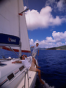 Two men relax aboard a yacht while sailing through the carribean waters off the British Virgin Islands