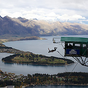 A participant jumps from the famous AJ Hackett Bungy Jump ' The Ledge' above Queenstown, New Zealand. The Bungy jump comes equipped with a runway to launch out 400 metres over Queenstown. with the Remarkables Mountain Range providing a stunning backdrop. Queenstown, Central Otago, South Island, New Zealand. 21st April 2011. Photo Tim Clayton..