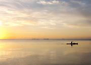 Fisherman paddles on Carribean Sea, Placencia, Belize