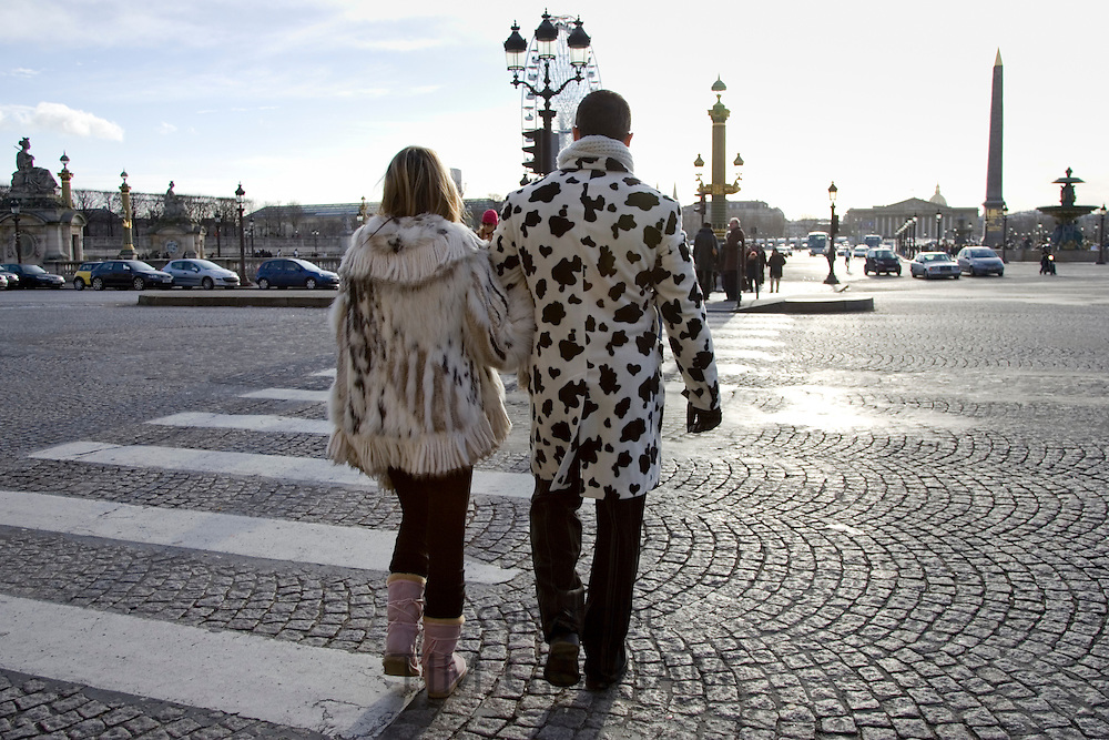 Pedestrians in winter coats walking across cobbled road on zebra crossing in Place de la Concorde, Central Paris, France