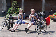 Twee oudere fietsers eten op het Binnenhof in Den Haag een boterham.<br /> <br /> Two elder cyclist are eating a sandwich at the Binnenhof in The Hague
