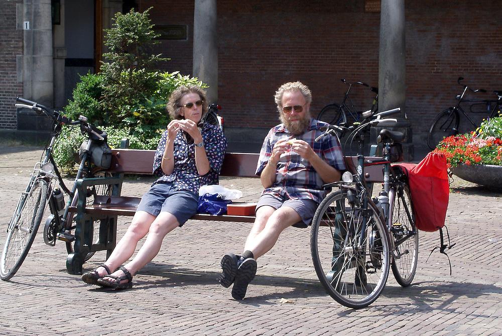 Twee oudere fietsers eten op het Binnenhof in Den Haag een boterham.<br /> <br /> Two elder cyclist are eating a sandwich at the Binnenhof in The Hague