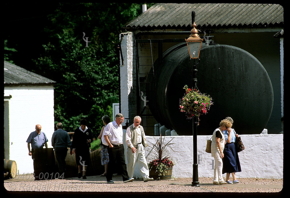 Visitors walk by old iron storage tank outside visitor center at Glenturret Distillery; Crieff. Scotland