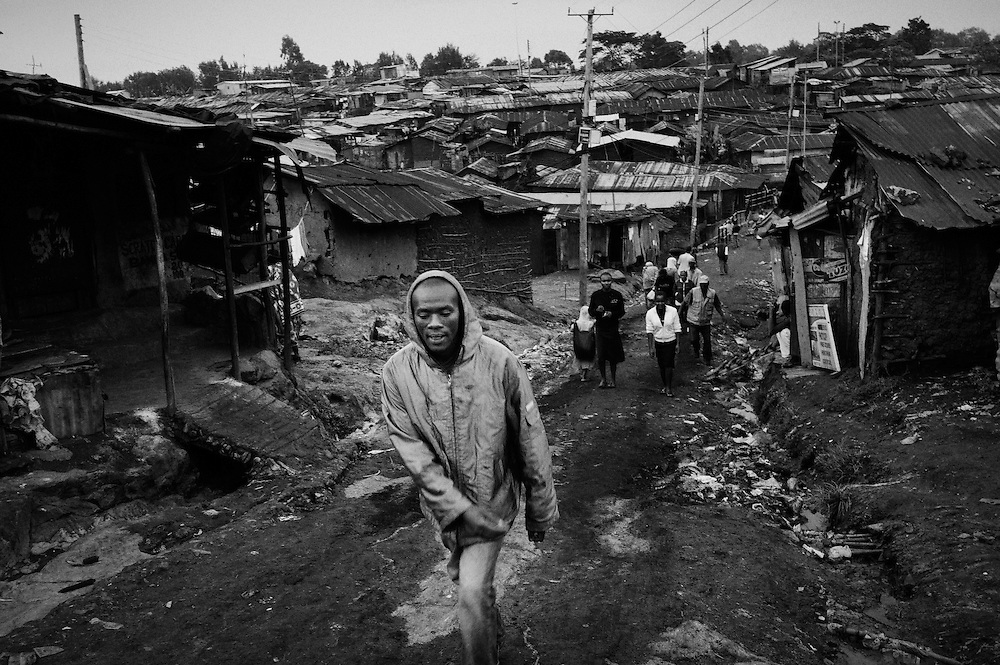"""NAIROBI, KENYA - AUGUST 16, 2011: Kamau """"Kelly"""" Ng'ang'a walks home through the winding dirt paths of Kibera slum.<br /> <br /> Within Kenya's progressive youth culture is the Kibera Olympic Boxing Club, a group of low-income adolescents from the slum whose leader uses boxing as a way to engage with idle youth. The group's ethnic diversity is remarkable given Kenya's 2008 post-election violence in which people from several tribes were forced violently out of slums. Together, these boxers represent a nascent trend of cross-tribe brotherhood in a healing nation."""