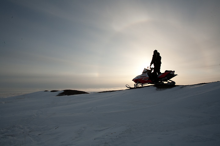 Framed by a sun dog, a lone hunter on snowmachine scans the Arctic Ocean near the Inupiat village of Point Hope, Alaska.