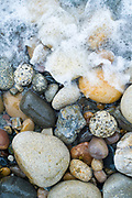 Pebbles in pastel shades of colour form curvy shapes on the seashore on Isle of Arran, Scotland