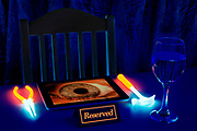 A reserved note sits in front of a able setting with a glowing hand tools and a tablet displaying an eerie eye.