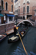 Gondolier steers gondola through canal using a large oar to maneuver, Venice, Italy..Subject photograph(s) are copyright Edward McCain. All rights are reserved except those specifically granted by Edward McCain in writing prior to publication...McCain Photography.211 S 4th Avenue.Tucson, AZ 85701-2103.(520) 623-1998.mobile: (520) 990-0999.fax: (520) 623-1190.http://www.mccainphoto.com.edward@mccainphoto.com.