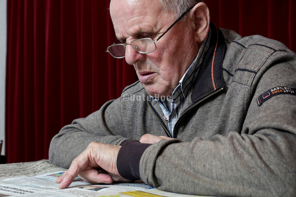 portrait of 89 year old man reading the newspaper