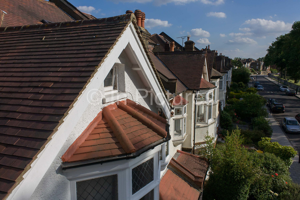 Aerial view of suburban Edwardian semi-detached houses in a south London street. We look down across the residential road in the borough of Lambeth where cars are parked and the sun shines on to the bay windows and roofs of middle-class houses built around the time of the first world war and whose building workforce probably did not return.