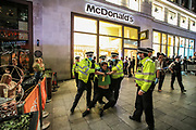 """Police dragged a handcuffed Extinction Rebellion activist who they said """"refused to walk"""" but he said he couldn't. The Activists occupied McDonald's in Leicester Square in central London on Tuesday, Aug 24, 2021.  XR is in an ongoing two-week protest campaign to demand that the government take greater action to address climate change. (VX Photo/ Vudi Xhymshiti)"""