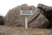 large Danger keep off the rocks sign by a small rock