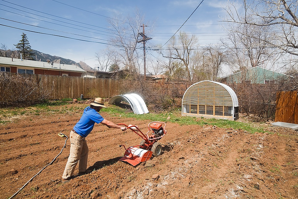 """Kipp Nash, founder of Community Roots Farm, plows a field in a private Boulder, Colorado backyard. Nash operates his """"Neighborhood Supported Agriculture"""" farm out of his neighbors' front and backyards."""