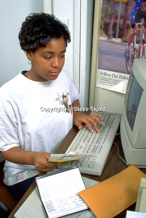 Worker age 16 going over finances at the Youth Express Bike Shop.  St Paul Minnesota USA
