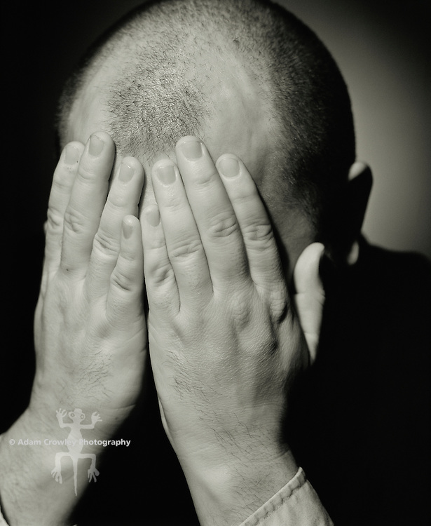 Middle-aged adult man (30-35 years old) with hands covering face, close-up (B&W)