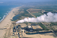 aerial over power generating electricity plant, steam, and smokestack along the beach on the Ventura County coast, California