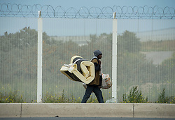 @ London News Pictures. 12/08/2015. Calais, France. A migrant carrying a mattress on his back as he walks along side a security fence near the migrant camp in Calis, referred to as The Jungle.. Photo credit: Ben Cawthra/LNP