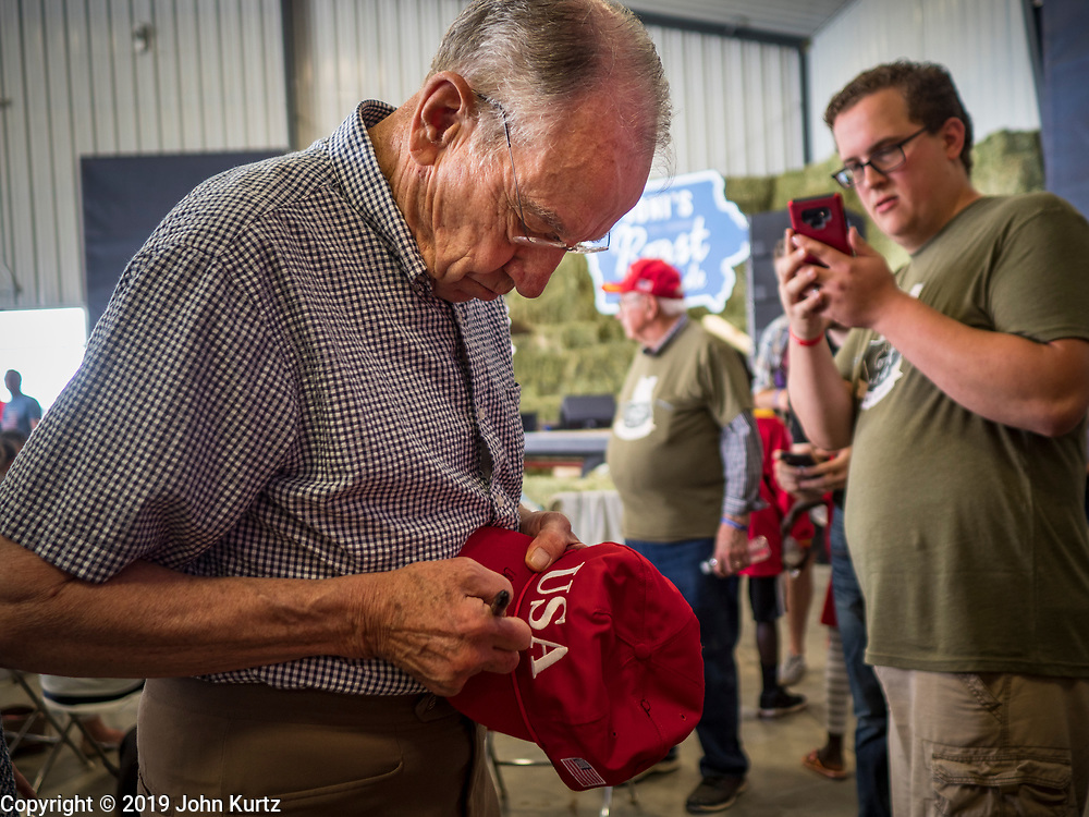 """15 JUNE 2019 - BOONE, IOWA: US Senator CHUCK GRASSLEY (R-IA) signs an autograph at """"Joni's Roast and Ride,"""" an annual fund raiser held by US Senator Joni Ernst (R-IA). Ernst, Iowa's junior US Senator, kicked off her re-election campaign during the """"Roast and Ride"""", an annual fund raiser and campaign event has she held since originally being elected to the US Senate in 2014.   PHOTO BY JACK KURTZ"""