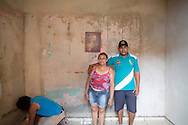 Rafael Teixeira and his mum, Complexo do Alemão 2013.<br /> Now 25 Rafael is living with his wife and 3 year old son in Complexo do Alemao. Rafael has overcome a lot of challenges in his life. In 2006 he had been struggling to stay out of working for the local drug faction he had just raised enough money to replace the roof to the room that he and his mother are standing in. Unfortunately he succumbed to a crack addiction for 2 years until he was helped by AfroReggae and a local church into rehab. He is now working with AfroReggae in Parada de Lucas on a project interviewing and photographing families in the community. He is proud of where he is today and is mainly focused on providing a good life for his wife and children. Part of the series Viver no Meio do Barulho (Living in the Middle of the Noise).