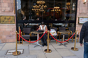 A woman customer sits with her laptop outside Caffe Concerto on Piccadilly during the second (Autumn) spike of the Coronavirus pandemic, on 5th October 2020, in London, England.
