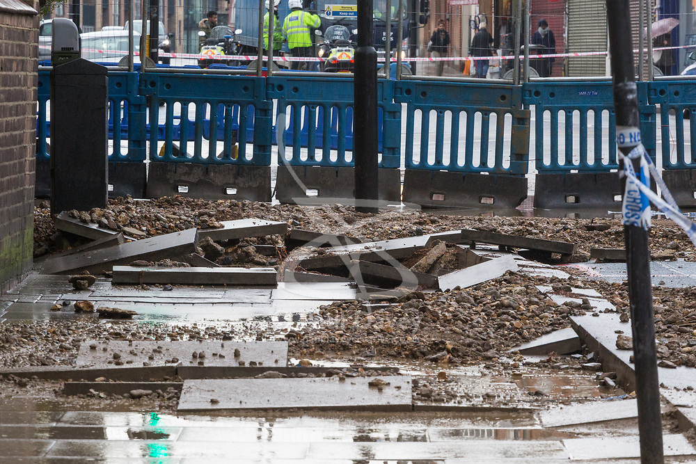 Displaced paving stones mark the site of yet another rupture water main in London. Workers clean up and prepare to dig up a large burst water main just yards from the entrance to Tooting Broadway station in South London. London water supply companies are battling a series of burst mains following the recent cold weather brought on by 'The Beast From The East'. London, March 07 2018.