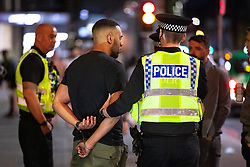 © Licensed to London News Pictures . 18/06/2021. Manchester, UK. Police cuff and detain a man on Peter Street , following the European Cup tie between England and Scotland at Wembley Stadium . Photo credit: Joel Goodman/LNP