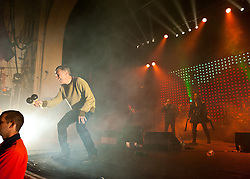 """© Licensed to London News Pictures. 10/05/2012. London, UK.  Happy Mondays perform live at O2 Academy Brixton.  In picture L to R Mark """"Bez"""" Berry (maracas), Shaun Ryder (vocals), Rowetta Satchell (maracas).  Photo credit : Richard Isaac/LNP"""