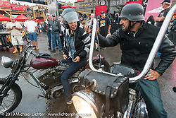 Wrench Magazine editor Cary Brobeck with his wife Karen leaving the very wet Easyriders Magazine Bike Show at the Easyriders Saloon during the annual Sturgis Black Hills Motorcycle Rally. SD, USA. August 5, 2014.  Photography ©2014 Michael Lichter.