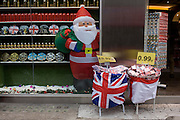 Tacky Christmas tourist trinkets on sale with a Santa theme outside a discount shop in New Oxford Street in central London.