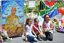 Young children in front of some of the condolence messages during a time of national mourning the death of the first democratically elected president, Nelson Mandela, in front of the Cape Town City Hall, Cape Town, South Africa, Saturday, 7th December 2013. Picture by Roger Sedres / i-Images