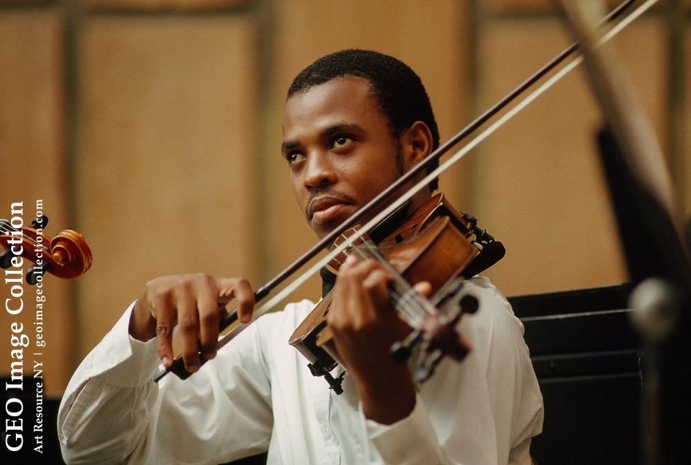 A young Haitian plays the violin with the St. Trinity Philharmonic.