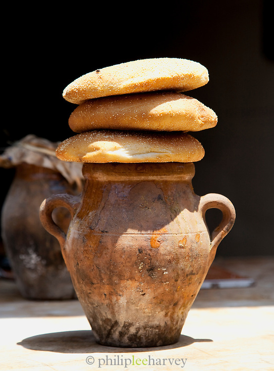 Fresh bread sitting on top of a jug used for cooking at a food stall in the medina of Marrakech, Morocco