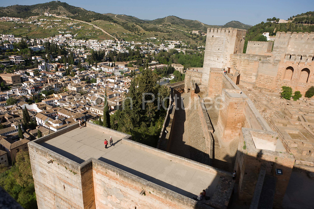 Two visitors walk along the rooftop of a section of Alhambra. This aerial landscape also shows in the background, the old Arab Albaicin quarter and surrounding barrios of Moorish city of Granada. The Albaicin Quarter is the old Moorish quarter across the River Darro from the Alhambra. When the Moors controlled Granada, this area of the city was the most densely populated. The streets are narrow and many of them do not have sidewalks. The houses are not very high and they are very close to each other. Alhambra (in Arabic, Al-Ḥamra) is a palace and fortress complex constructed during the mid 14th century by the Moorish rulers of the Emirate of Granada in Al-Andalus.