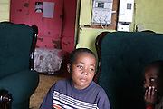 Zanoxolo, 9, a boy living with HIV, is sitting in his home in the township of Khayelitsha, Cape Town. He lives with the mum, also HIV+ and 2 brothers.