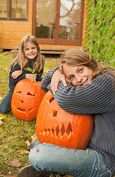 Sisters sitting with halloween pumpkin, smiling, portrait