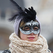 VENICE, ITALY - FEBRUARY 11:  A woman wearing a Carnival mask watches a show in St Mark's Square on February 11, 2012 in Venice, Italy.The annual festival, which lasts nearly three weeks, will see the streets and canals of Venice filled with people wearing highly-decorative and imaginative carnival costumes and masks.