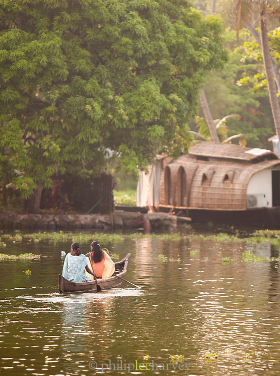 Two women paddle towards a house boat near Alappuzha in the Kerala Backwaters, India