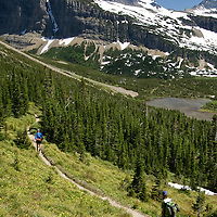 Hikers descend toward Atsina Lake from Stoney Indian Pass in Glacier National Park's backcountry.