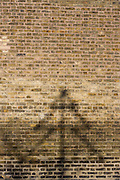 The shadow of a Christmas tree display from an adjacent Xmas shop, on a brick wall.