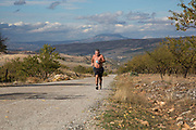 Man out running in the heat through olive groves near to Alhama de Granada, Andalucia, Spain. This is a totally agricultural area, covered mainly with olives. It is a distinctly Mediterranean landscape where blue skies and green life prevails.