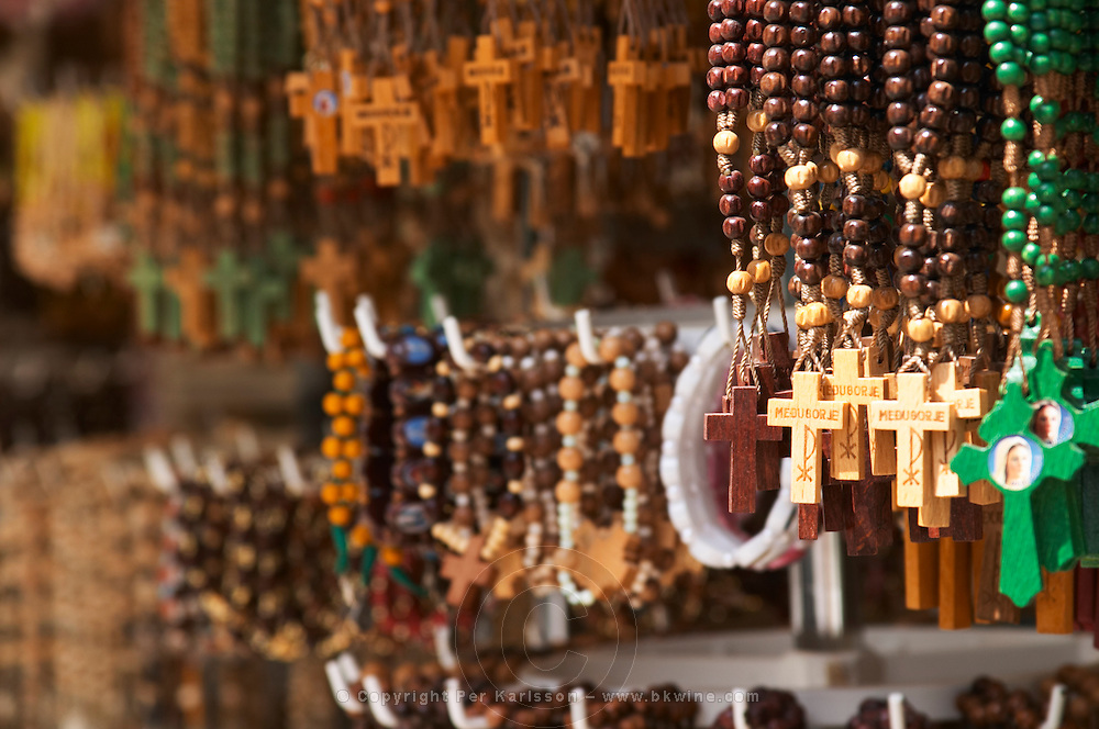 A shop with souvenirs for pilgrims, with things for sale. Rosary beads, with crosses with the name Medugorje on. Medugorje pilgrimage village, near Mostar. Medjugorje. Federation Bosne i Hercegovine. Bosnia Herzegovina, Europe.