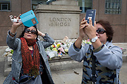 Three days after the terrorist attack in which 7 people died and many others suffered life-changing injuries on London Bridge and Borough Market, tourists take tragedy selfies by the shrine of flower tributes, on 6th June 2017, on London Bridge, in the south London borough of Southwark, England. City commuters now back at work walk respectfully and quietly past the floral memorial at the plinth marking the southern boundary of the City of London, the capitals financial district.